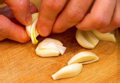 zbývající česnek je nakrájíme spolu na čtvrtiny nacpat šunku do trouby
