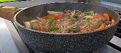 добавляем в говядину на сковороде нарезанный имбирь с чесноком и перемешиваем